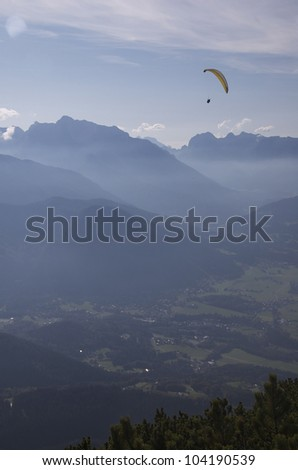 Mountain Para glider- A para-glider soars over an Alpine valley - stock photo