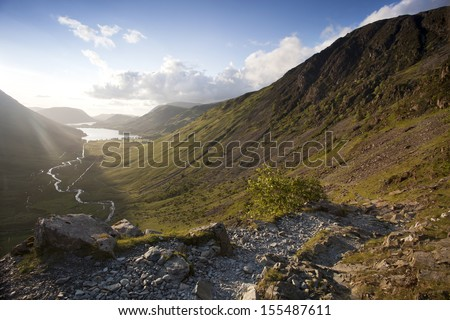 mountain path to the sunset looking down the valley towards buttermere, cumbria - stock photo