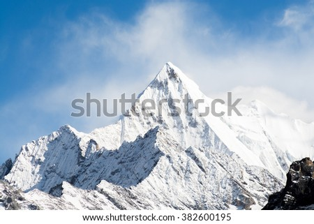 Mountain peak with snow in mist, Yading national level reserve, Daocheng, Sichuan Province, China