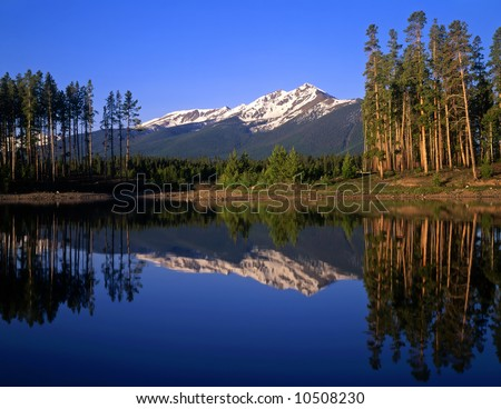 Mountain peaks and trees reflecting in Lake Dillon located in the Arapaho National Forest of Colorado. - stock photo