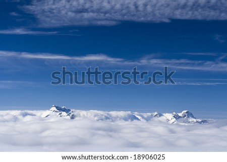 Mountain peaks from the clouds and blue sky