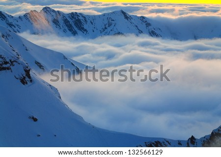 Mountain peaks in winter rising at sunset above thick layer of clouds - stock photo