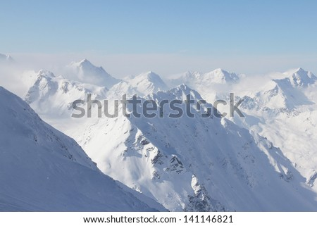 Mountain peaks of winter alps under blue sky