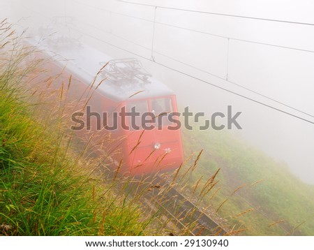 Mountain railway in the mist, Swiss Alps - stock photo