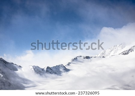 Mountain range in Alps with snow and wind