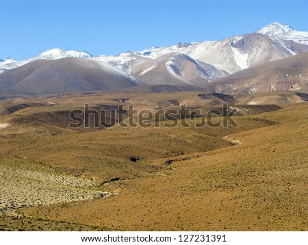 mountain range in Chile with peaks in snow seen from Atacama desert