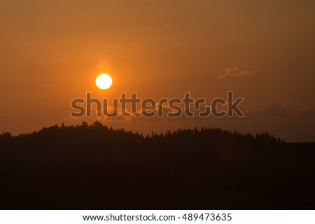 Mountain range on the background of the sunset with clouds