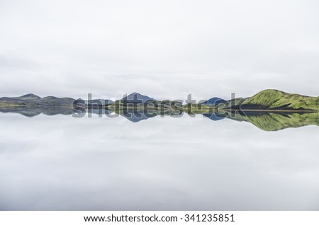 mountain range reflecting in lake - stock photo