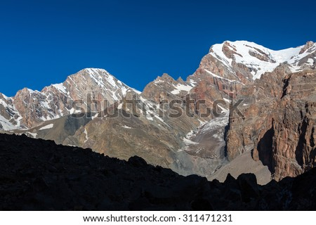 Mountain Range View. Morning Sunlight Landscape of Summits Peaks Ridge with Steep Rock Walls and Glaciers on Top at Fan Mountains Valley of Tajikistan - stock photo