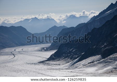 Mountain range with large glacier between mountains - stock photo