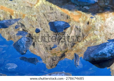 Mountain reflected in the lake. Reflection of a rocky summit in water, the Slovakian Tatra Mountains. - stock photo