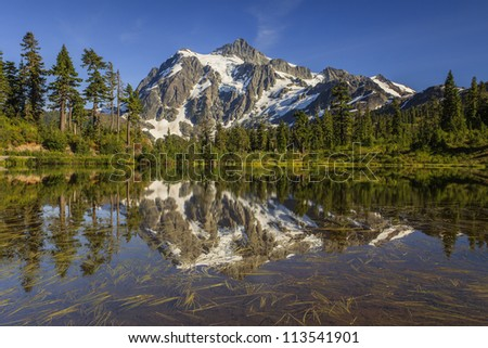 Mountain reflection by the lake - stock photo