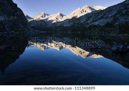 mountain reflections in Long Lake in Rock Creek of the Sierra Nevada Mountains - stock photo