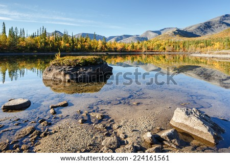Mountain ridge and northern taiga forest reflected in shallow Polygonal freshwater lake with rocks in foreground, Hibiny mountains above the Arctic Circle, Russia - stock photo