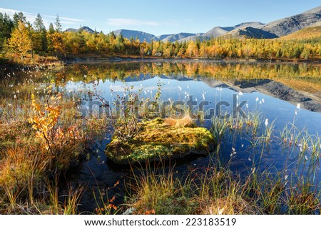 Mountain ridge reflected in shallow Polygonal freshwater lake with bog hummocks in foreground, Hibiny mountains above the Arctic Circle, Russia - stock photo