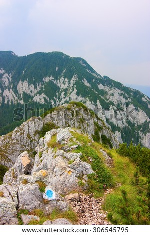 Mountain ridge with peak in the background on a cloudy day - stock photo