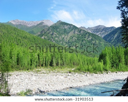 Mountain, river and forest landscape with blue sky - stock photo