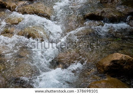 Mountain river flowing, water and rocks covered with moss under water - stock photo