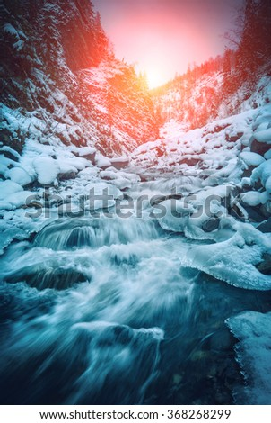 Mountain river in a light of sunrise. Dramatic and picturesque wintry scene. Carpathian, Ukraine, Europe. Beauty world. Glowing filter.