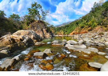 Mountain river in the Himalayas flows among the rocky stones steep shores. Uttarakhand, India - stock photo