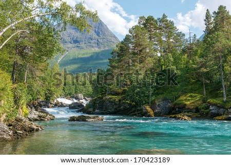Mountain river passing in green Norwegian mountains - stock photo