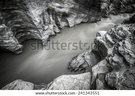 Mountain river running through the rocky canyon. Long exposure black and white shot - stock photo