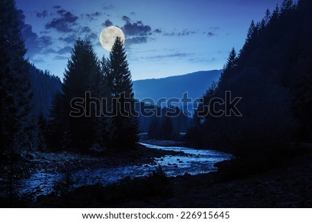 mountain river with stones and moss in the forest near the mountain slope at night in full moon light - stock photo