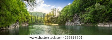 mountain river with stones on the shore in the forest near the mountain slope - stock photo