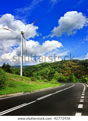 Mountain road and wind turbine - stock photo