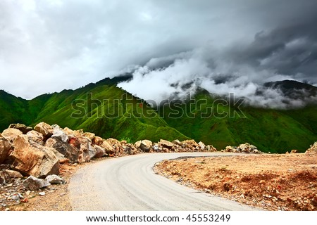 Mountain road at rainy day with clouds on the sky - stock photo