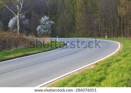 Mountain road bending with road signs - stock photo