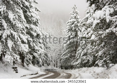 Mountain road covered with snow - stock photo