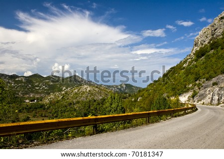 Mountain road in sunny day - stock photo