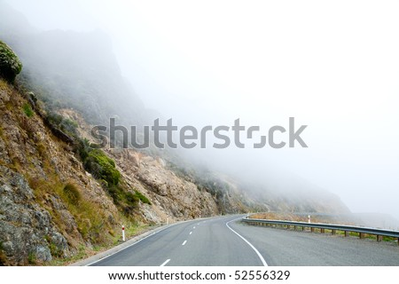 Mountain road in the Southern Alps of New Zealand  on a foggy day - stock photo