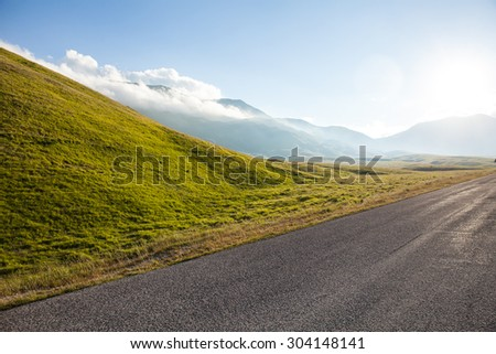 Mountain road in the sunset light. Blue sky with clouds background - stock photo