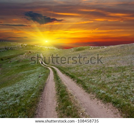 Mountain road on sunset background - stock photo