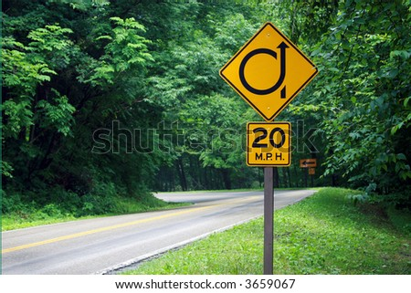 Mountain road sign warning of a tight, 360 degree turn ahead. - stock photo