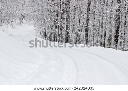 Mountain road snow covered in the forest. Road in snow. - stock photo