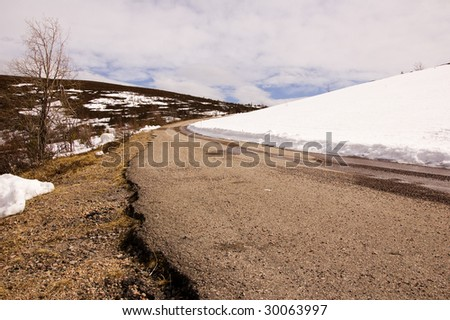 Mountain road, snow on the right side - stock photo