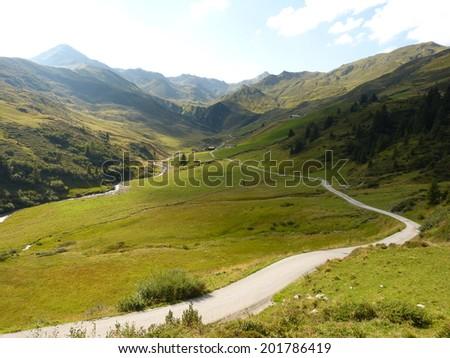 Mountain road through the Alps - stock photo