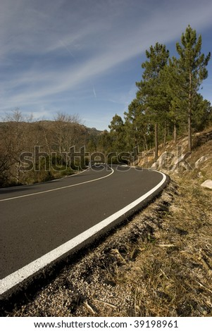 Mountain road with many curves, in blue sky background