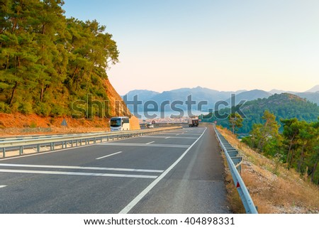 mountain road with turns and transport - stock photo