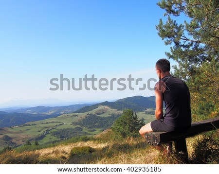 Mountain runner athlete sitting on bench and relaxing, looking into the distance. Summer, Pieniny, Poland. - stock photo