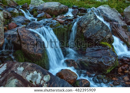 Mountain's creek flowing along stones