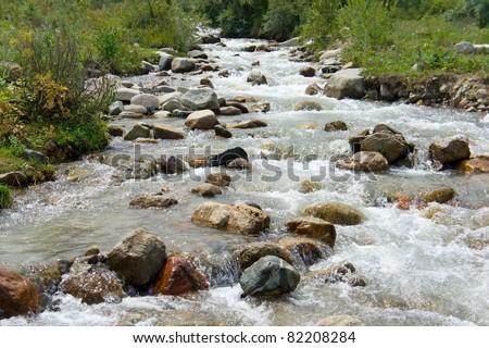 Mountain's River in the Alps. Forest stream running over rocks. - stock photo