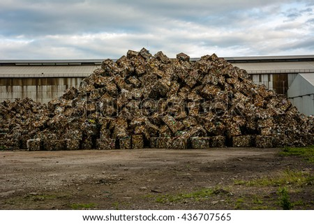 mountain Scrap Steel ready for recycling over dark clouds. - stock photo