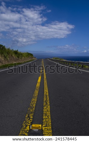 Mountain side road heading towards sea - stock photo