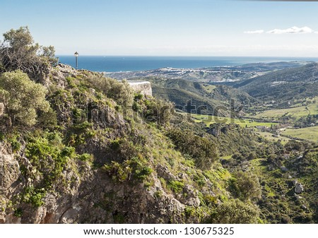 Mountain situated in the Spanish village of Casares located in the province of Malaga, in one side you can see the pointview with a lamp post and in the background the mediterranean sea - stock photo