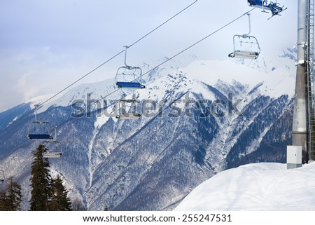 Mountain ski chair lift ropeway and snowy peaks - stock photo