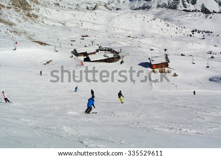 Mountain ski resort. Skiers and snowboarders going down the slope. - stock photo